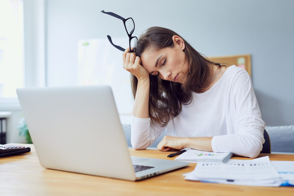 A woman feeling tired while at work, for Crown Point dental treatment turn to our skilled dentist.