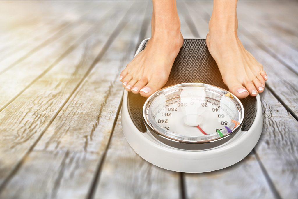 Feet standing on scale for weight gain concept, contact dentist office in Winfield for solutions to weight gain due to dental issues.
