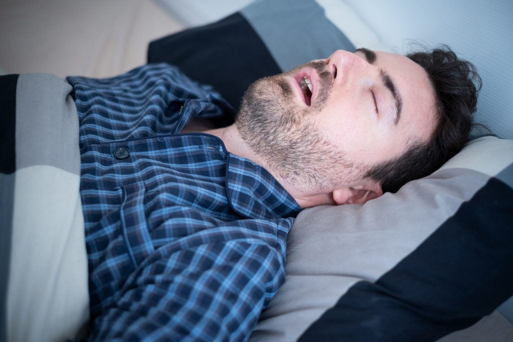 Man sleeping on back with mouth open, for Oral Health Issue Crown Point from sleeping concern visit CP dentist.