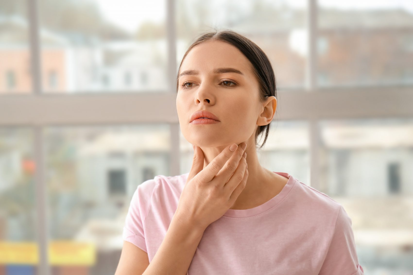 Woman checking her thyroid problems at home, our Crown Point Dentist Office can treat your dental condition.