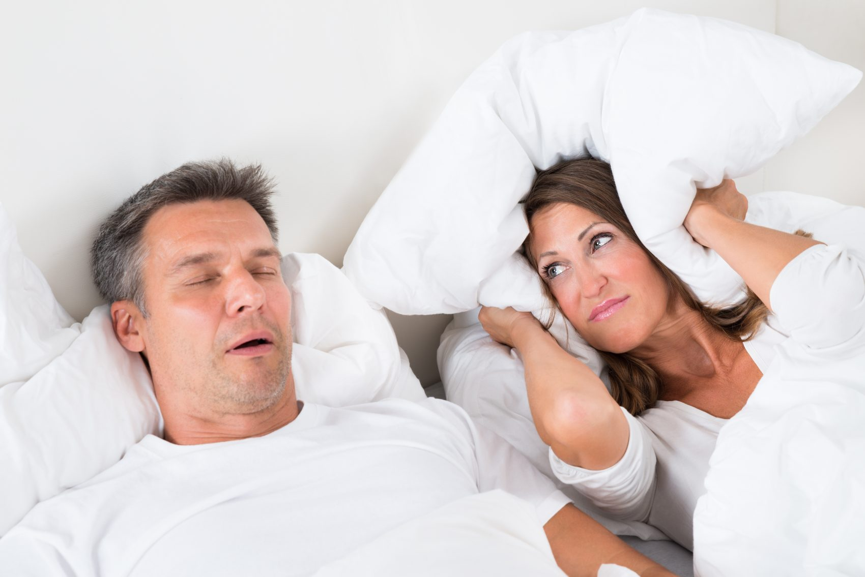 Woman covering her ears with pillow as man is snoring, for help with snoring call NW Indiana Dental Office.